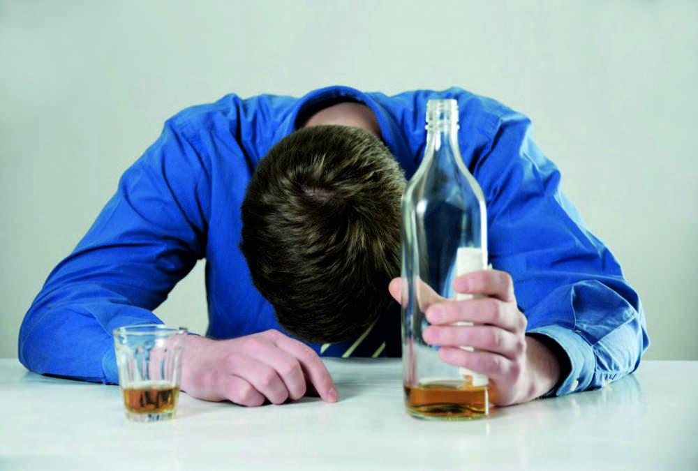 Мужчина в синей рубашке с бутылкой алкоголя в руках спит на столе